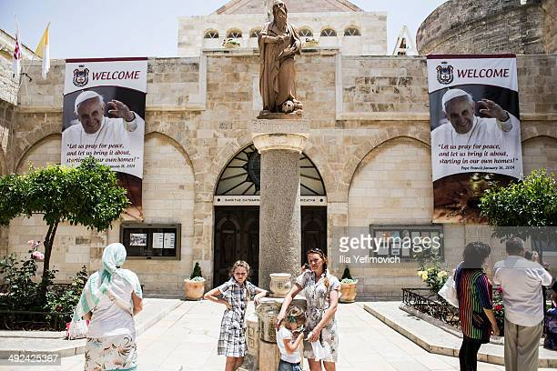 Tourists gather at the church of Nativity tin front of posters of Pope Francis on May 20 2014 in Bethlehem West Bank Pope Francis is due to make his...