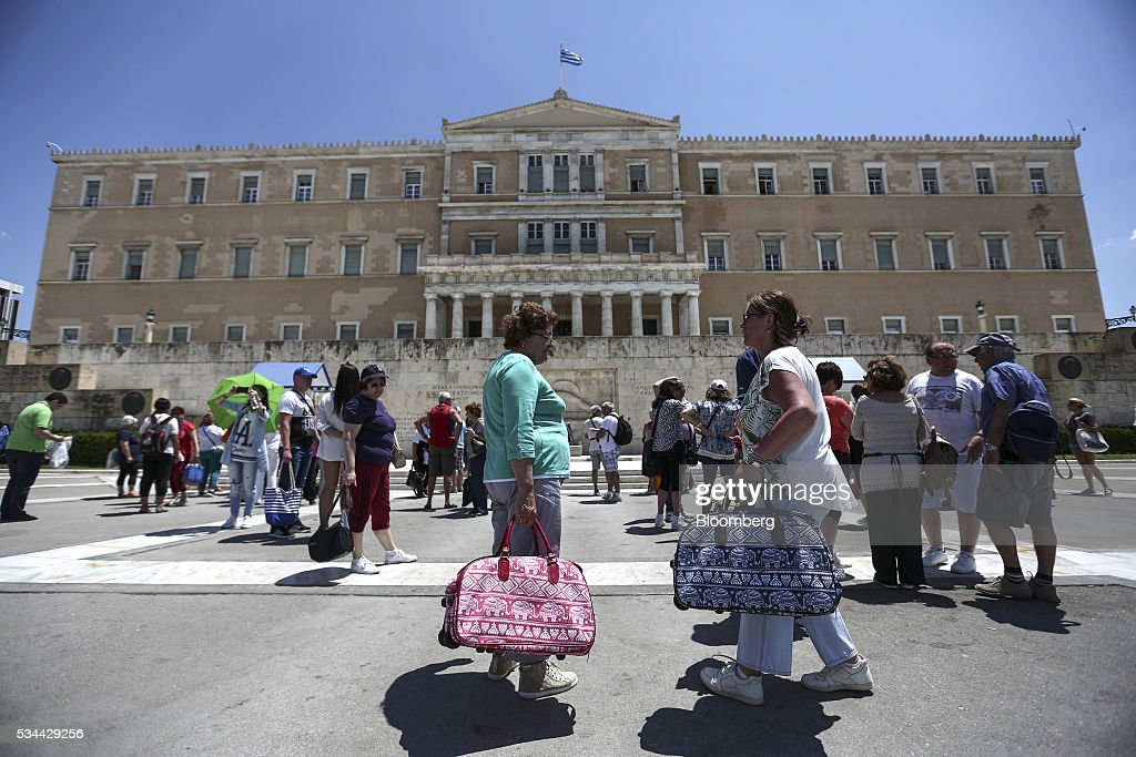 Tourists gather outside the Greek parliament building to watch presidential guards perform their ceremonial duties on Syntagma Square in Athens, Greece, on Thursday, May 26, 2016. Greece may have passed a milestone and its bond market has been lucrative for some investors, but the road to recovery doesn't look much shorter. Photographer: Yorgos Karahalis/Bloomberg via Getty Images