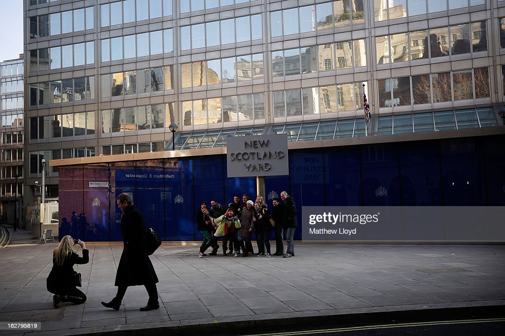 Tourists have a group picture taken in front of New Scotland Yard in the sunshine on February 27, 2013 in London, England. The Met Office has predicted a cold period at Easter.