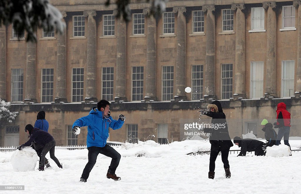 Tourists have a snow ball fight in front of the Royal Crescent overlooking Victoria Park on January 18, 2013 in Bath, England. Heavy snow is bringing widespread disruption to many parts of the UK.