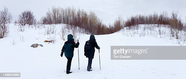 Tourists hiking by frozen lake in the Arctic Circle on Ringvassoya Island in the region of Tromso Northern Norway