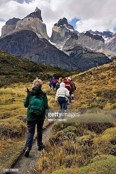Tourists hiking with Los Cuernos in the background. Torres del Paine National Park, Chile