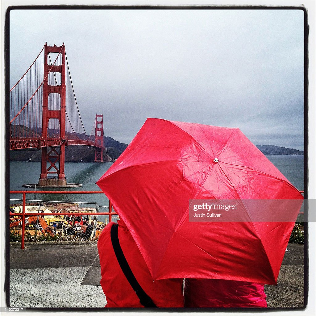 Tourists hold an umbrella near the Golden Gate Bridge on May 2, 2012 in San Francisco, California. The Golden Gate Bridge, Highway and Transportation District is preparing for the 75th anniversary of the iconic Golden Gate Bridge that will be marked with a festival on May 26 - 27 that will feature music, displays of bridge artifacts and art exhibits. The 1.7 mile steel suspension bridge, one of the modern Wonders of the World, opened to traffic on May 27, 1937.