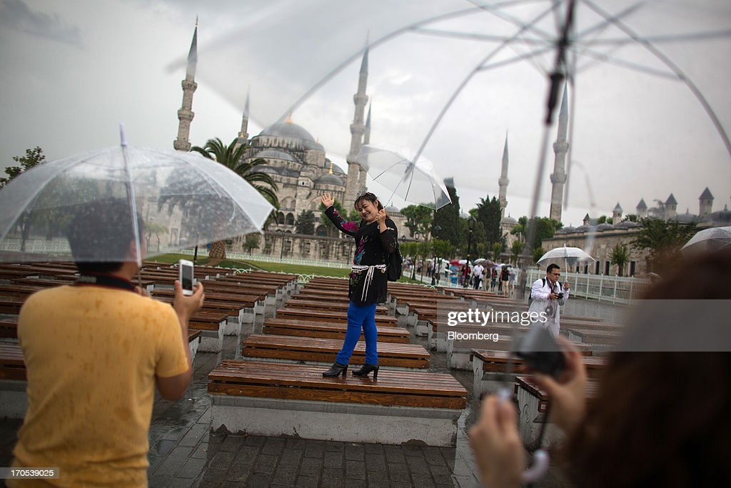Tourists hold umbrellas while posing for photographs outside the Blue Mosque, also known as the Sultan Ahmed, in Istanbul, Turkey, on Friday, June 14, 2013. The law forbids the sale of alcohol at night and near schools and mosques, going against the secular traditions of the Muslim-majority country of 74 million, where many people drink and women often choose not to cover their hair. Photographer: Lam Yik Fei/Bloomberg via Getty Images