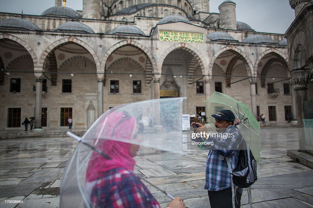 Tourists hold umbrellas while sheltering from the rain in the central square inside the Blue Mosque, also known as the Sultan Ahmed, in Istanbul, Turkey, on Friday, June 14, 2013. The law forbids the sale of alcohol at night and near schools and mosques, going against the secular traditions of the Muslim-majority country of 74 million, where many people drink and women often choose not to cover their hair. Photographer: Lam Yik Fei/Bloomberg via Getty Images