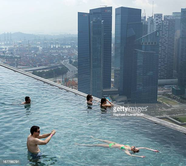 Tourists in a swimming pool on the roof garden of the Marina Bay Sands Resort with the skyline in the backgroundon February 09 2013 in Singapore...