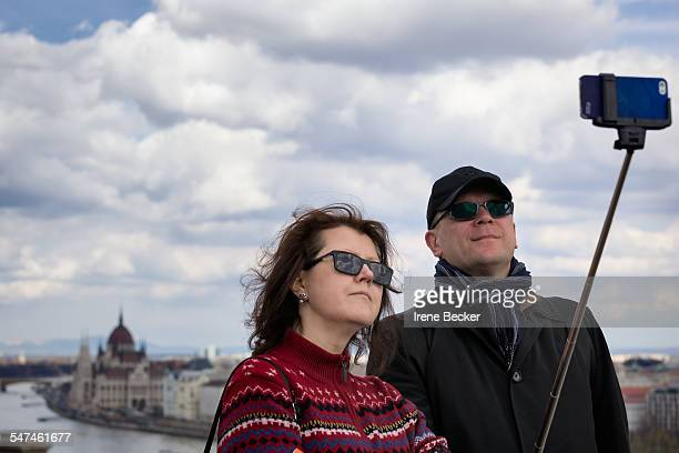 Tourists in Budapest using a selfie stick to take a photo whit Hungarian Parlament Building in background