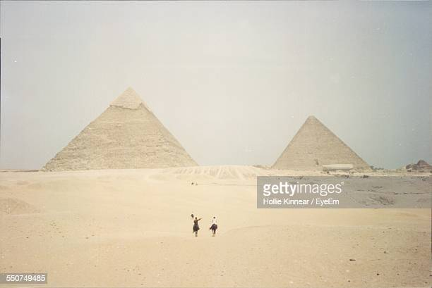 Tourists In Front Of Pyramids Against Clear Sky