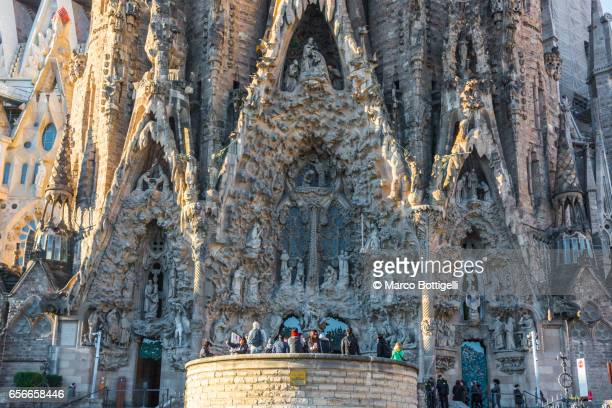 Tourists in front of the facade of the Sagrada Familia. Barcelona, Spain