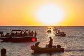 Tourists in motorboats watching golden sunset San Antonio, Ibiza, Spain
