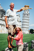A happy couple smile at the camera as they pose for a picture near the Leaning Tower of Pisa. The man is standing on a railing holding his hat up to make it look like it is on top of the tower.