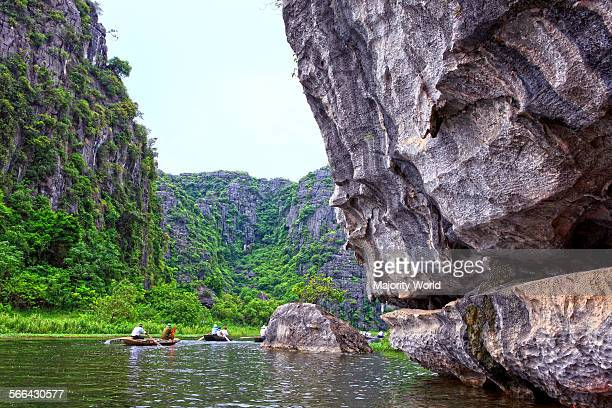 Tourists in row boats explore the Ngo Dong river through karstic limestone mountains at Tam Coc near Ninh Binh Tam Coc was created due to the...