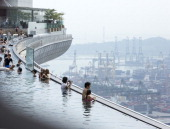 Tourists in the swimming pool on the roof garden of the Marina Bay Sands Resort with a view of the harbor in the background on February 09 2013 in...