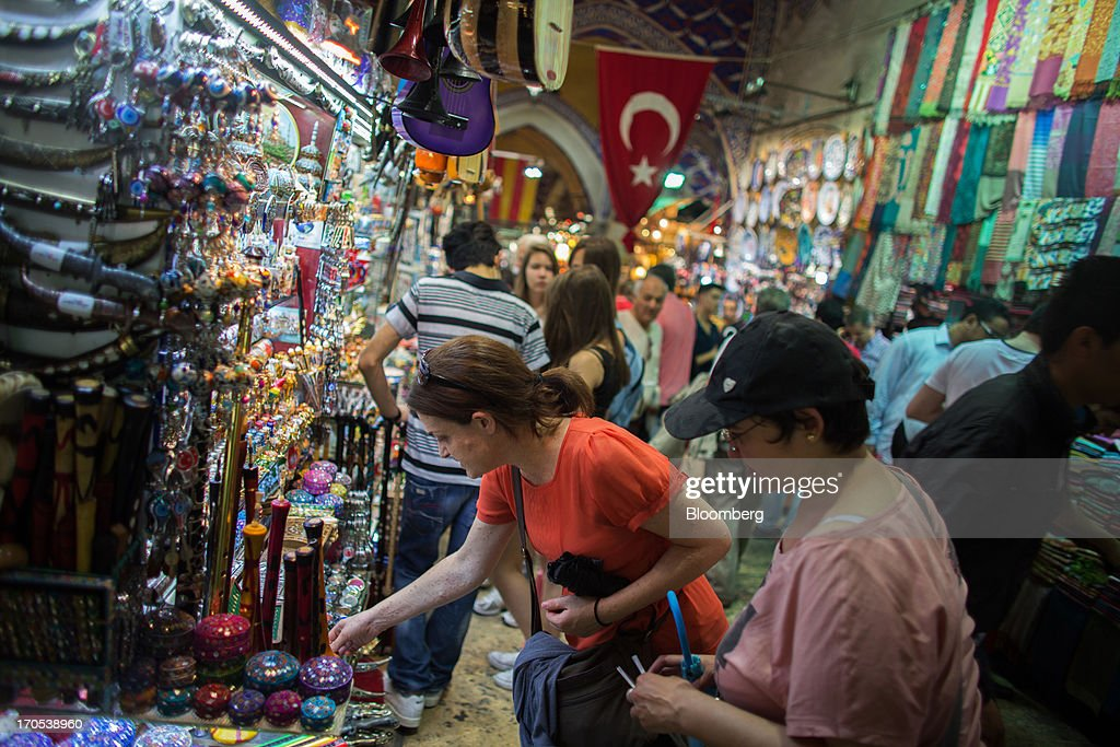 Tourists inspect goods for sale outside souvenir stores in the Grand Bazaar covered market in Istanbul, Turkey, on Friday, June 14, 2013. The law forbids the sale of alcohol at night and near schools and mosques, going against the secular traditions of the Muslim-majority country of 74 million, where many people drink and women often choose not to cover their hair. Photographer: Lam Yik Fei/Bloomberg via Getty Images