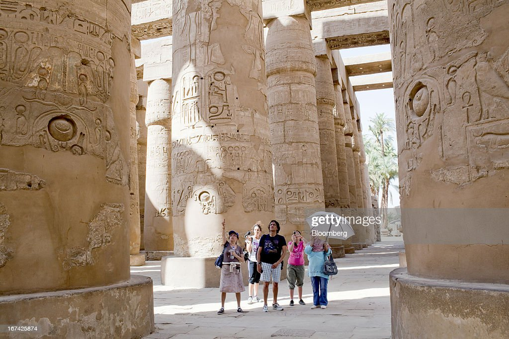 Tourists inspect the ruins of Karnak temple in Luxor, Egypt, on Thursday, April 25, 2013. Egypt ranked last in terms of security and safety on the World Economic Forum's 2013 Travel and Tourism Competitiveness Index. Photographer: Shawn Baldwin/Bloomberg via Getty Images