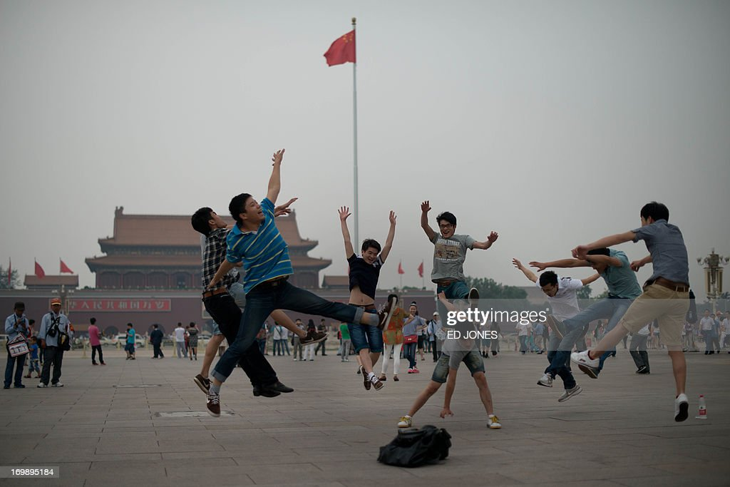 Tourists jump as their friends take photos on Tiananmen square in Beijing on June 4, 2013. Authorities launch a major push every June 4 to prevent discussion of the violently crushed 1989 pro-democracy protests, in which at least hundreds of people died. AFP PHOTO / Ed Jones