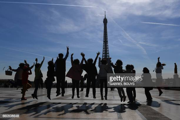 TOPSHOT Tourists jump as they pose for a family photo on the Esplanade du Trocadero near the Eiffel Tower in Paris on March 30 2017 / AFP PHOTO /...