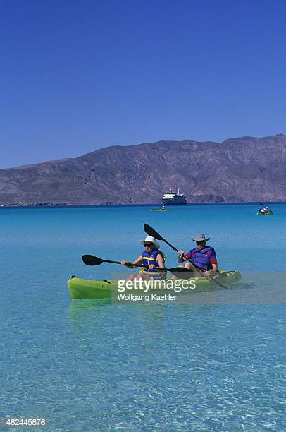 Tourists kayaking in front of Coronado Island in Baja California Mexico with cruise ship Endeavour in background