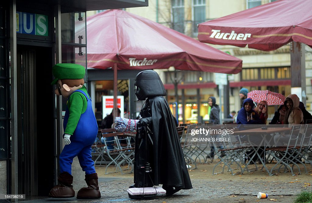 Tourists laugh as street artists dressed up as Darth Vader and Super Mario enter a subway station at the Brandenburg Gate in Berlin, Germany on October 25, 2012.