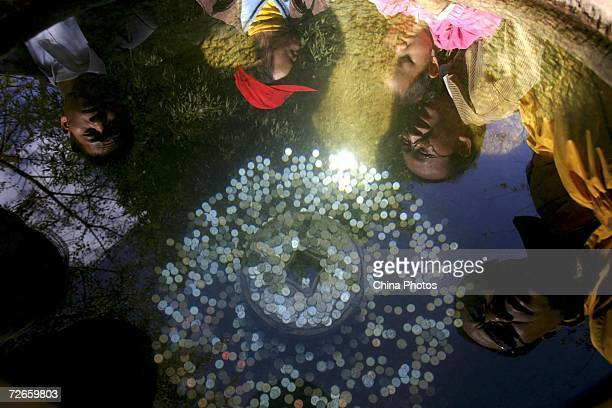 OUT Tourists lay coins into a fountain pool to pray for good luck at a park which is famous for Blackheaded Gulls November 27 2006 in Kunming of...