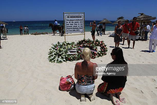 Tourists lay flowers in memory of the victims of a terror attack outside the Imperial Marhaba Hotel in the popular tourist resort of alSousse Tunisia...
