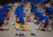 Tourists lay on rows of sun umbrellas on Playa Blaca beach on April 13 2014 in Lanzarote Spain Lanzarote where British Prime Minister David Cameron...