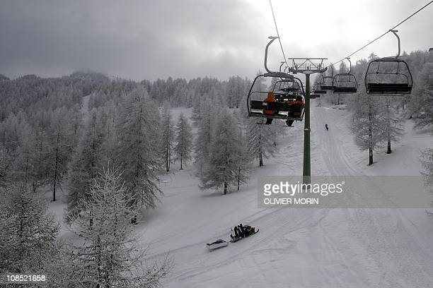 Tourists leave the slope on a ski lift after the official cancellation of the Women's World Cup downhill on January 29 2011 in Sestriere Thick fog...