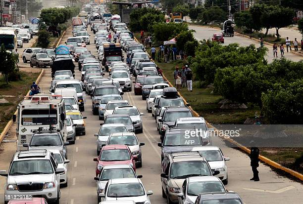 Tourists leave town after an alternate way to get to Mexico City was opened on September 20 2013 in Acapulco Mexico as some 25000 are still looking...