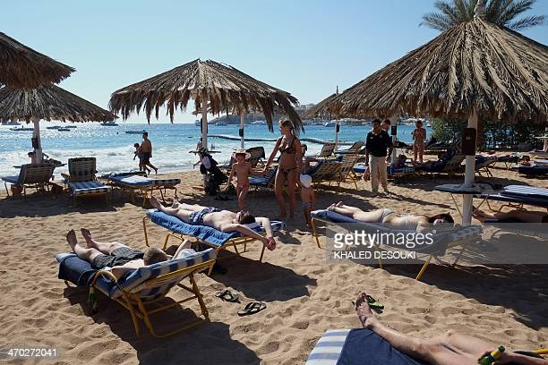 Tourists lie on beach beds at a hotel in the Egyptian Red Sea resort of Sharm elSheikh on February 19 2014 The decline in tourism since the fall of...
