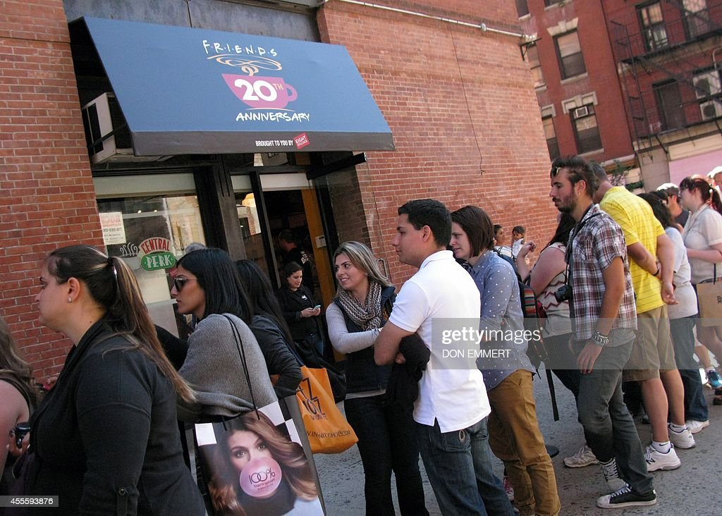 Tourists line up outside a temporary 'pop up' reproduction of the 'Central Perk' coffee shop a center piece set of the television situation comedy...