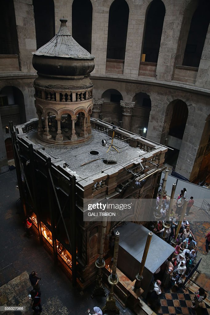 Tourists line up to enter the Tomb of Jesus as they stand under a metal scaffolding built at the entrance ahead of the restoration on May 29, 2016 at the Church of the Holy Sepulchre in Jerusalem's Old City. The tomb where Jesus is said to have been buried before his resurrection, is to undergo major restoration. The restoration entrusted to a Greek team, is expected to be completed in early 2017 and the site will remain open to visitors in the meantime. / AFP / GALI