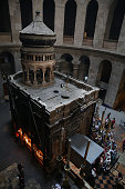 Tourists line up to enter the Tomb of Jesus as they stand under a metal scaffolding placed at the entrance on May 29 at the Church of the Holy...