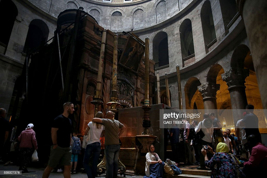 Tourists line up to enter the Tomb of Jesus as they stand under a metal scaffolding built at the entrance ahead of the restoration on May 29, 2016, at the Church of the Holy Sepulchre in Jerusalem's Old City. The tomb where Jesus is said to have been buried before his resurrection, is to undergo major restoration. The restoration entrusted to a Greek team, is expected to be completed in early 2017 and the site will remain open to visitors in the meantime. / AFP / GALI