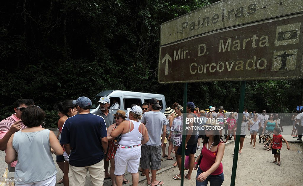 Tourists line up to take a van to access to the Christ the Redeemer statue, atop the Corcovado hill on January 25, 2013 in Rio de Janeiro, Brazil. During summer season around three thousand of tourists line up about three hours to visit the traditional statue. AFP PHOTO / ANTONIO SCORZA