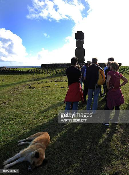 Tourists liste to explanatios from a guide in fron of a Moais stone statue of the Rapa Nui culture on Easter Island 3700 km off the Chilean coast in...