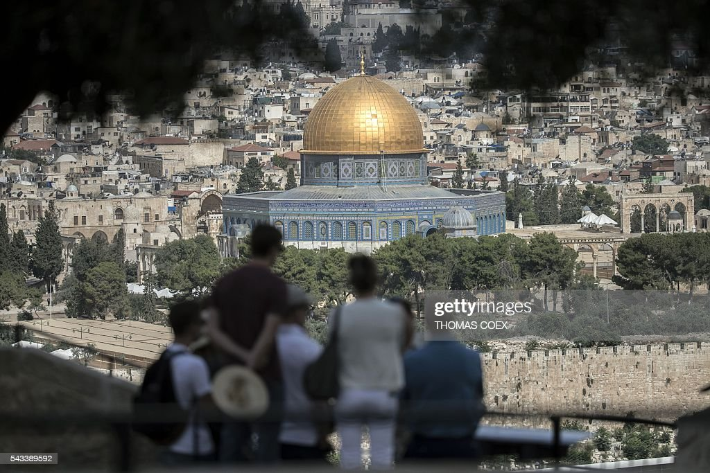 Tourists listen to a guide during a visit at Mount of Olives in east Jerusalem overlooking the Old City and the Dome of the Rock mosque, situated at the Al-Aqsa mosque compound, on June 28, 2016. Israeli authorities announced they were closing Jerusalem's flashpoint Al-Aqsa mosque compound to non-Muslim visitors after a series of clashes between worshippers and police. COEX