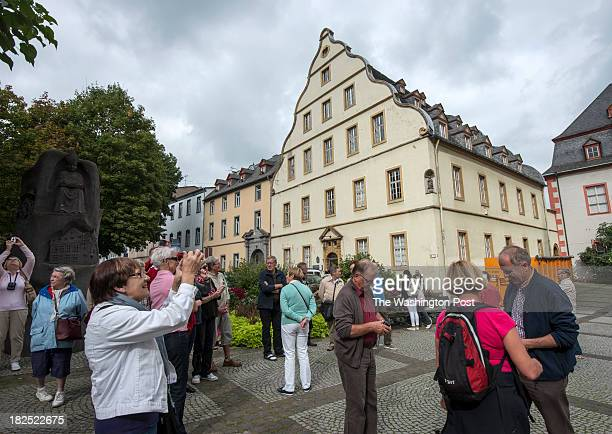 Tourists listen to a guide's explanations and take pictures in front of the Buerresheimer hof in Florinsmarkt Koblenz Germany 23 September 2013 The...