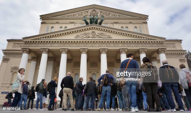 Tourists listen to their guide as they gather in front of the Bolshoi Theatre in central Moscow on July 10 2017 Russia's Bolshoi theatre announced on...