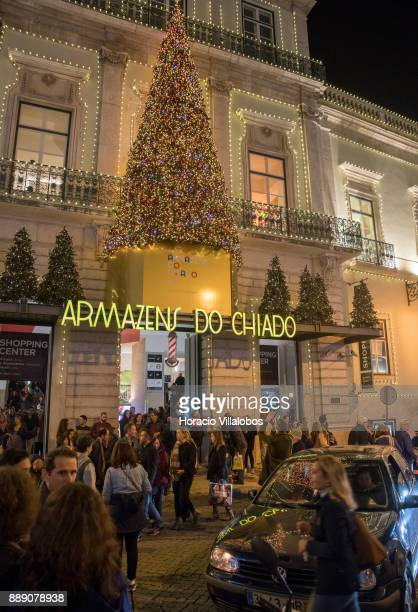 Tourists locals and shoppers are seen under Armazens do Chiado Shopping Center Christmas and New Year light displays at the end of Rua Garrett on...