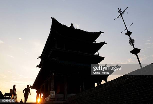 Tourists look around atop the old city gate on September 21 2008 in Pingyao of Shanxi Province China Pingyao with a history of over 2700 years is a...