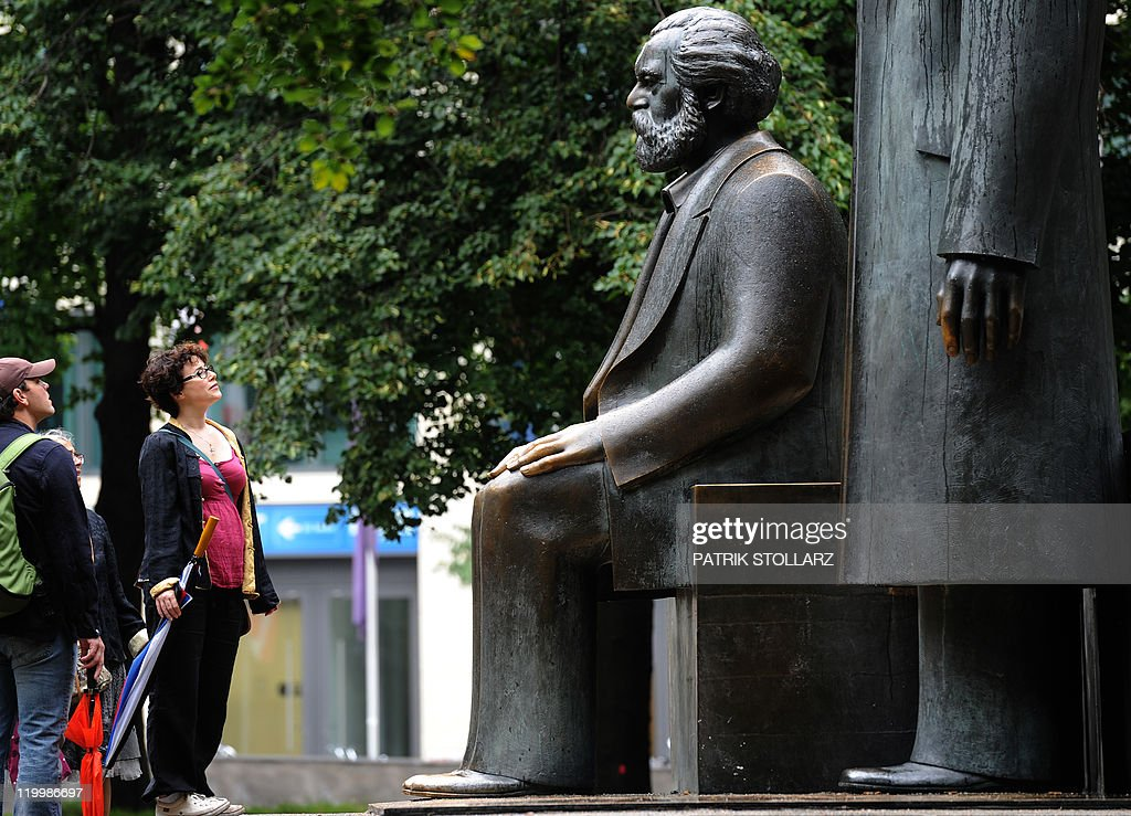 Tourists look at a bronze statue of German philosopher, sociologist and economic historian Karl Marx on July 28, 2011 in Berlin. The monument, which also includes a statue of German industrialist and social scientist Friedrich Engels, has become an icon of the early communism ideology. It was built by east German sculptor Ludwig Engelhardt and inaugurated in 1986.