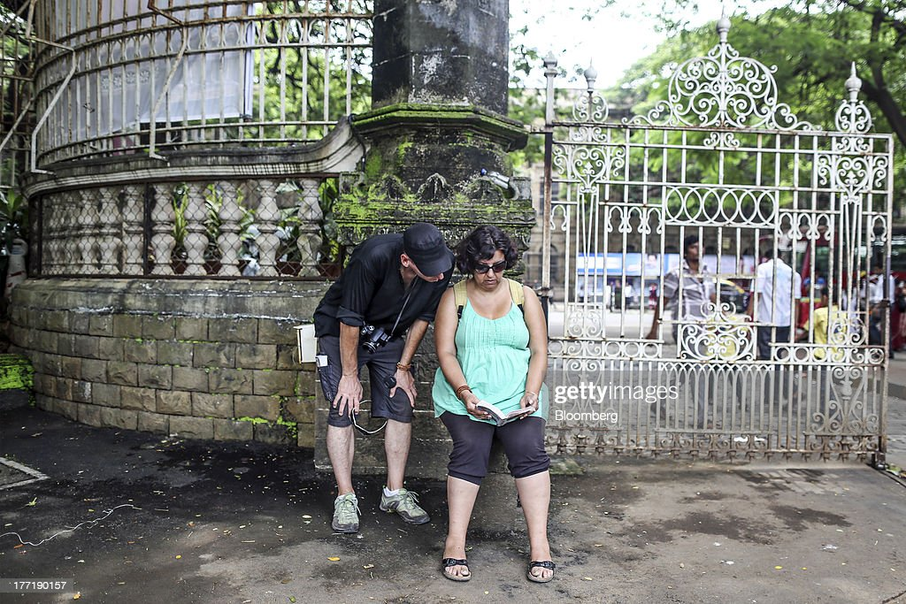 Tourists look at a guidebook at the gates of The Chhatrapati Shivaji Maharaj Vastu Sangrahalaya museum in Mumbai, India, on Wednesday, Aug. 21, 2013. The prospect of an indecisive 2014 election in India is eroding confidence among global investors that the government can stop the rupees worst drop in more than two decades. Photographer: Dhiraj Singh/Bloomberg via Getty Images
