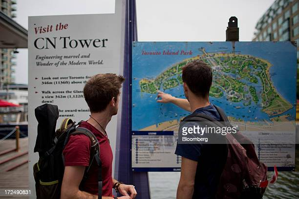 Tourists look at a map of Toronto Island Park in Toronto Ontario Canada on Monday July 1 2013 Total arrivals from Canadian Tourism Commissions...