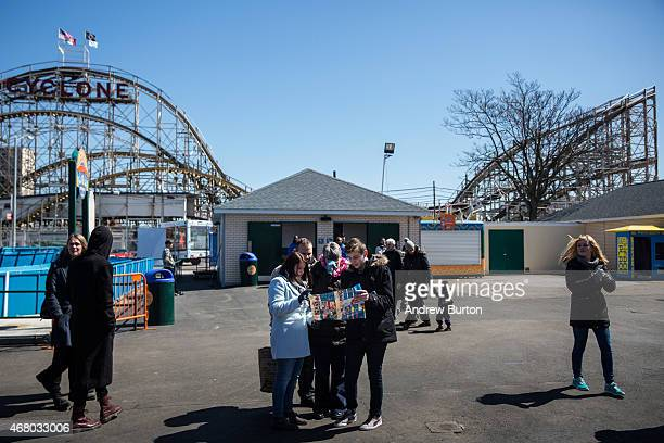 Tourists look at a map while visiting Coney Island on March 29 2015 in New York City Various Coney Island businesses including Luna Park opened for...