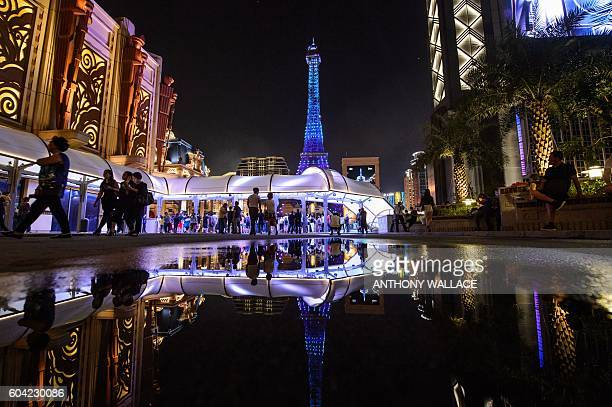 Tourists look at a replica of the Eiffel Tower after the opening of the Sands new mega resort The Parisian in Macau on September 13 2016 Billionaire...