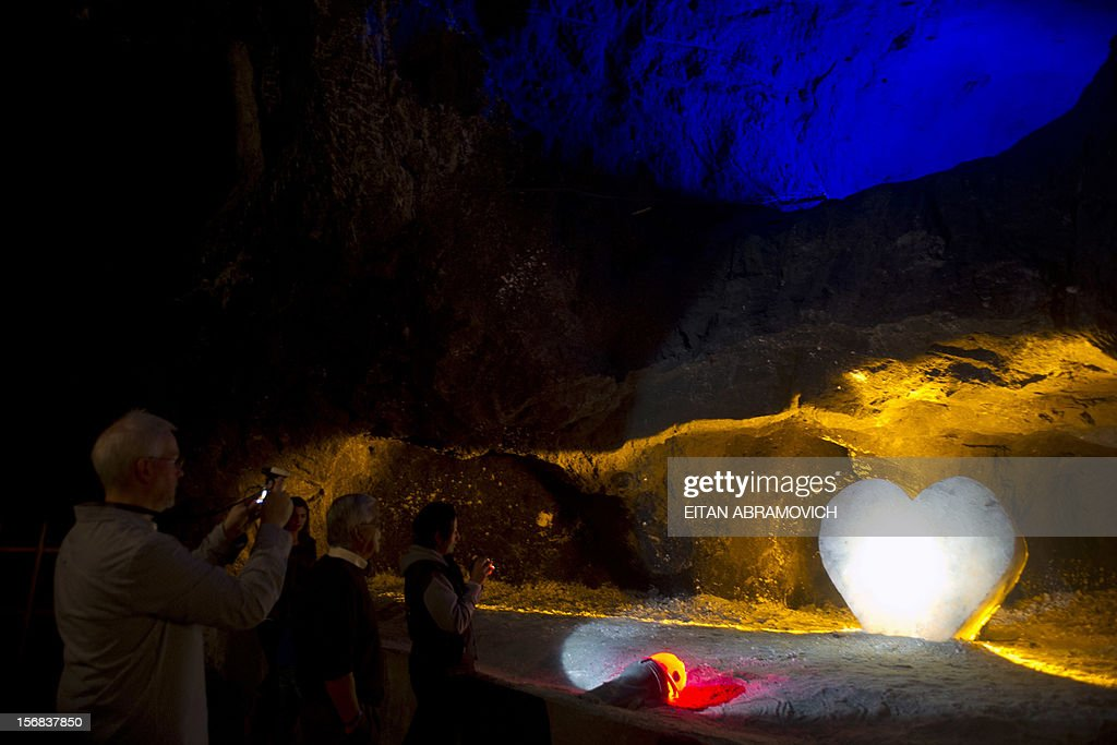 Tourists look at a salt crystal weighing 1,600 kg, carved into the shape of a heart at Nemocon's salt mine in Nemocon, Cundinamarca, Colombia on November 22, 2012. The mine, an impressive construction at 80 meters of depth with over 500 years of history, has become a new attractive tourist destination in Colombia. AFP PHOTO/Eitan Abramovich