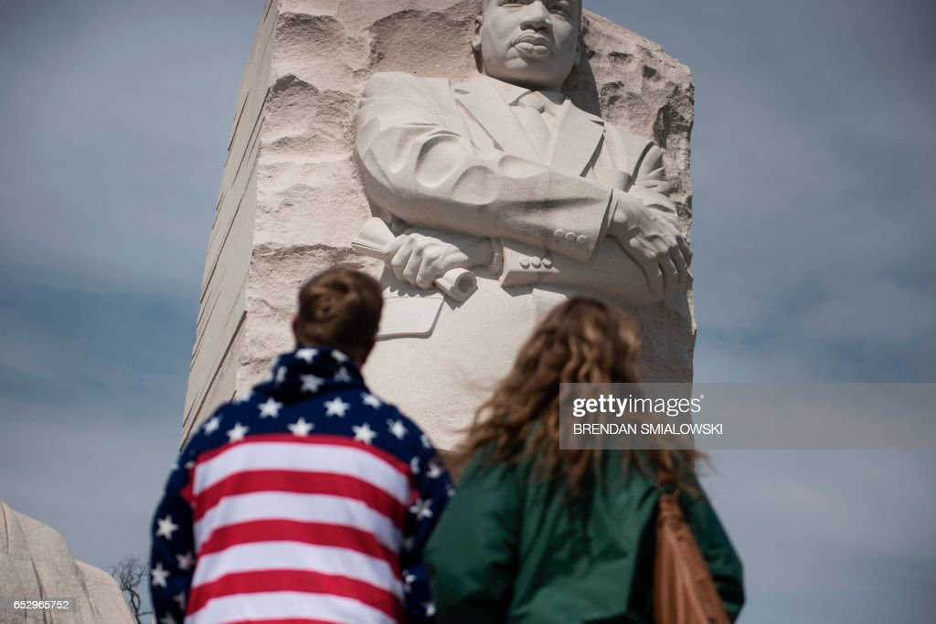 Tourists look at a statue of Martin Luther King Jr. on the National Mall on March 13, 2017 in Washington, DC. / AFP PHOTO / Brendan Smialowski