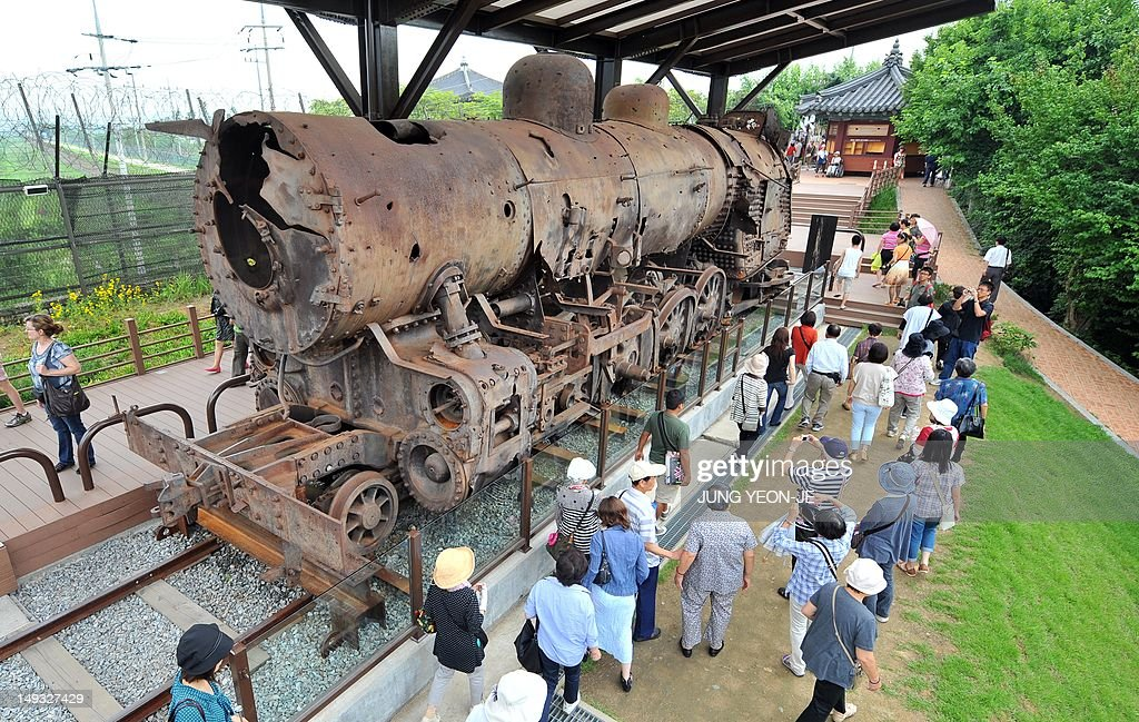 Tourists look at a steam locomotive damaged after being derailed by bombing during the Korean War on display at Imjingak peace park in Paju, near the demilitarized zone dividing the two Koreas on July 27, 2012, on the day of the 59th anniversary of signing the Korean War armistice. The armistice agreement on July 27, 1953 brought three years of active combat in the Korean War to a halt, but the two Koreas are still technically at war as no formal peace treaty was signed.