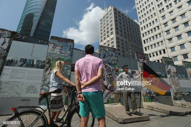 Tourists look at an actor dressed in an East German military uniform and posing with a flag of the former East Germany at a surviving portion of the...