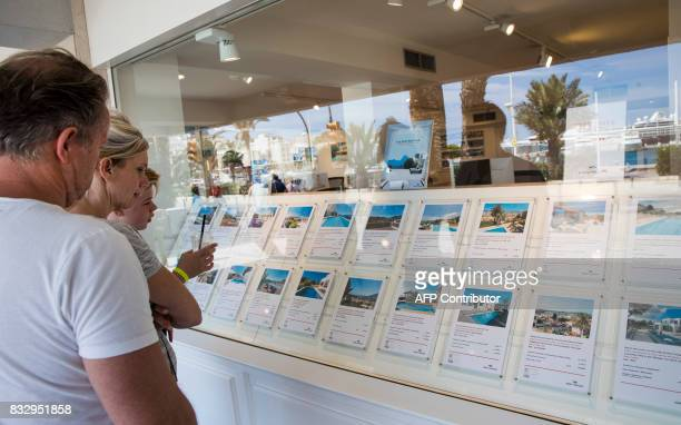 Tourists look at apartments in the window shop of a real estate on the island of Ibiza on August 11 2017 Known as much as a wild party island as a...